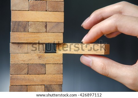 Closeup hand man take one block on The tower from wooden blocks, dark tone. Risk.