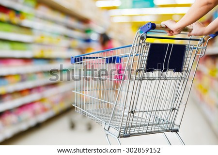 closeup hand pushing shopping cart in groceries store - stock photo