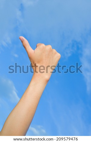 Closeup hand thumbs up sign blue sky - stock photo