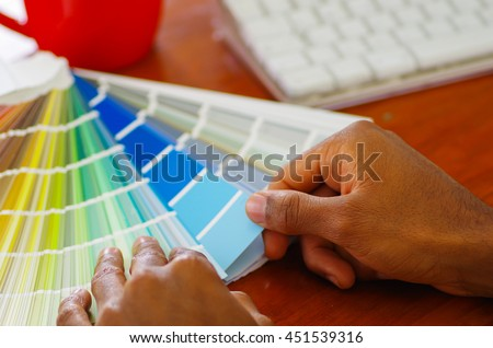 Closeup hands holding palette, colormap spread out in front of white computer keyboard, designer concept