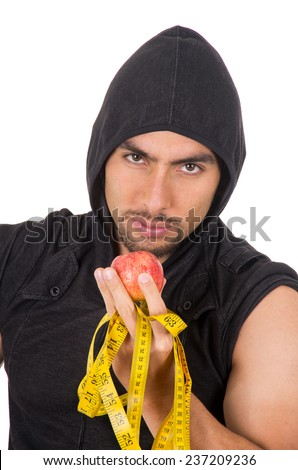 closeup handsome athletic young latin man wearing hoodie holding red apple and measuring tape concept of diet  isolated on white