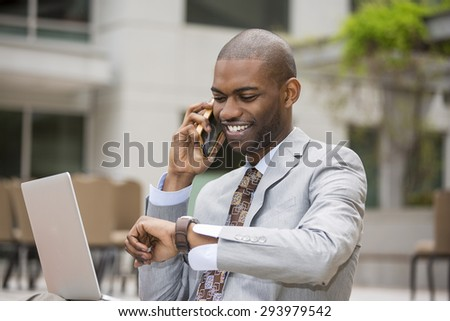 Closeup handsome young businessman working with laptop outdoors talking on mobile phone looking at his wristwatch. Time is money  - stock photo
