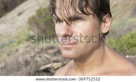 Closeup head shot of serious Caucasian male beach bum surfer dude with long hair hanging in face looking away from camera - stock photo