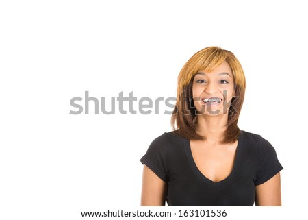 Closeup head shot portrait of smiling young happy woman looking at camera gesture with good news isolated on white background with copy space to left. Positive human emotions and facial expressions - stock photo