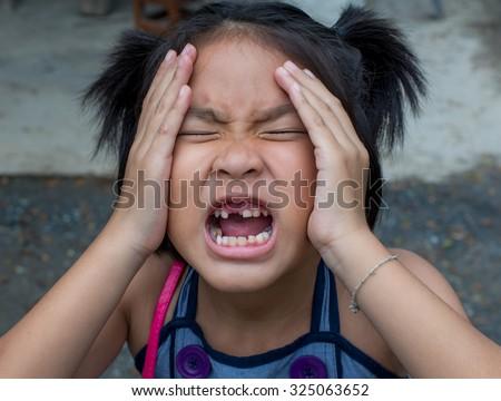 Closeup headache little asian girl with a broken teeth - stock photo