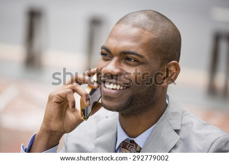 Closeup headshot handsome happy laughing young businessman talking on mobile phone outdoors - stock photo