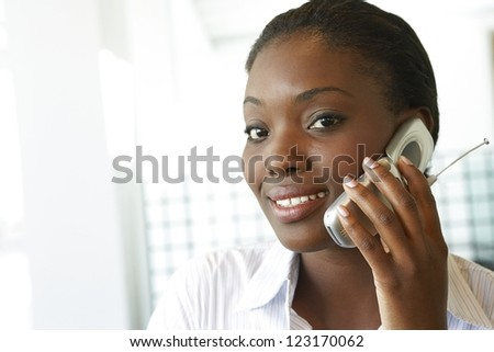 Closeup headshot of a smiling attractive African woman talking on a mobile phone - stock photo