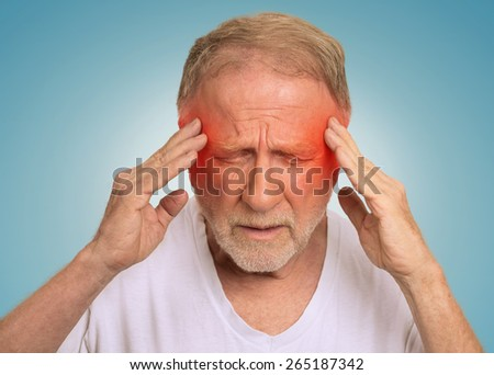 Closeup headshot senior man suffering from headache hands on head with red colored inflamed areas looking down isolated on light blue background. Human face expression. Health problems issues  - stock photo