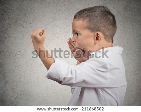Closeup Headshot side view Portrait Angry Child Screaming, fists up in air isolated grey wall background. Negative Human face Expressions, Emotion, Reaction, Perception. Conflict confrontation concept - stock photo