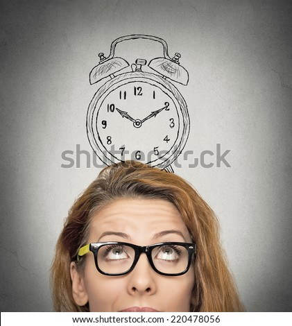 closeup headshot young business woman with alarm clock drawing sketch above her head, isolated grey wall background. Human face expressions, emotions. Time, punctuality, busy schedule concept - stock photo