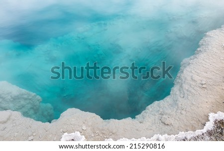 Closeup horizontal image of a deep aqua color hot spring hole in Yellowstone National Park  - stock photo