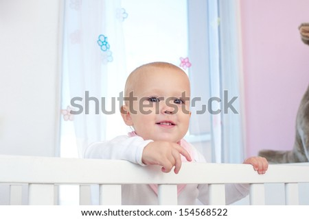 Closeup horizontal portrait of an adorable baby smiling in crib