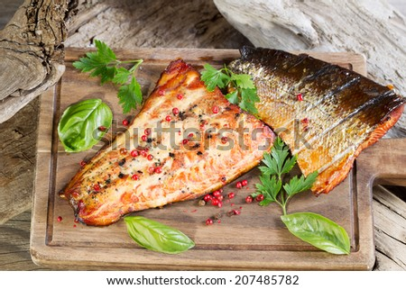 Closeup horizontal view of smoked salmon fillets with seasoning inside of drift wood on serving board - stock photo