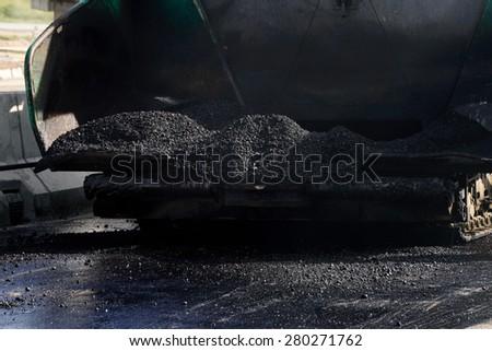 closeup hot asphalt in the hopper of asphalt paver machine - stock photo