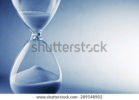 Closeup hourglass clock on light blue background