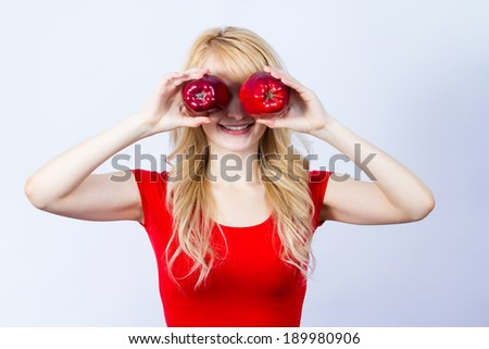 Closeup, humorous portrait young, happy, smiling woman, girl holding two apples, covering her eyes, isolated blue background. Positive human emotions, life perception, approach, healthy life style