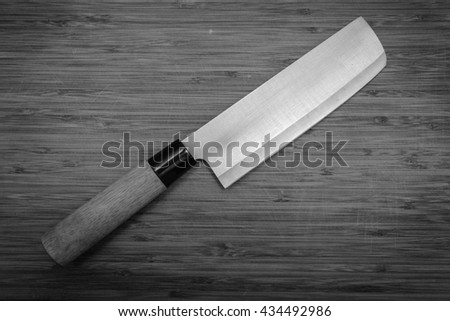 Closeup image black and white of kitchen japanese style chef knife on vintage cutting board