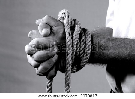 Closeup image from a man's tied hands praying - black & white - stock photo