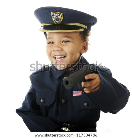 Closeup image of a delighted preschooler wielding a toy guy in his policeman uniform.  Motion blur on hand and gun.  On a white background. - stock photo