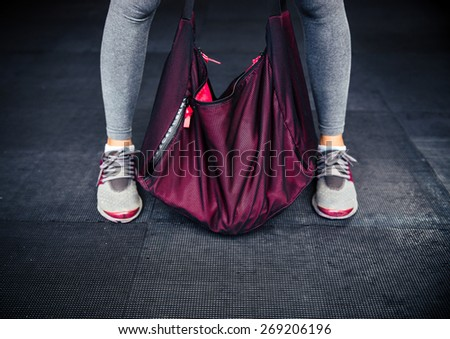 Closeup image of a female legs and sports bag - stock photo