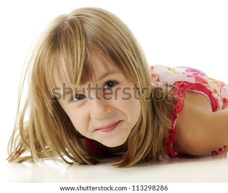 Closeup image of a happy young elementary girl who is lifting her head to look at the viewer from her belly-down position on the floor.  On a white background.