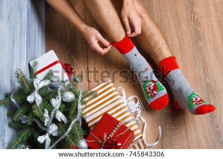 Closeup image of a man who adjusts his New Year's woolen socks.