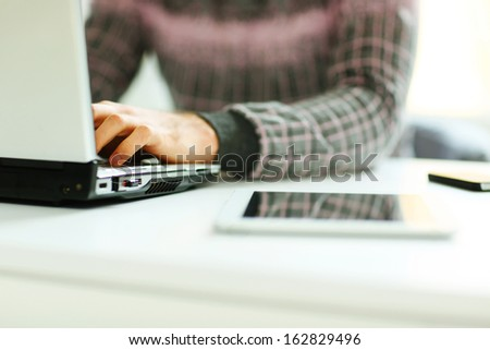 Closeup image of a man working on laptop at his workplace - stock photo