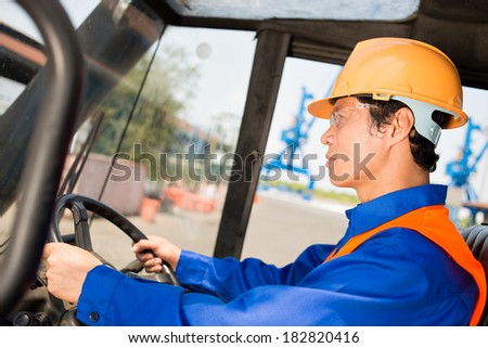 Closeup image of a port docker in uniform driving a machine on the foreground  - stock photo