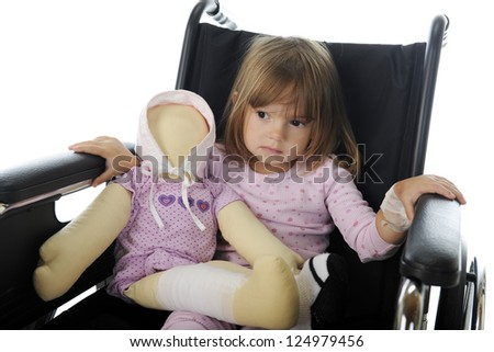 Closeup image of a sad little girl sitting in a wheelchair in her pajamas.  She has a doll with bandages like hers. - stock photo