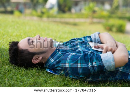 Closeup image of a student with a tablet lying on the grass in the campus  - stock photo