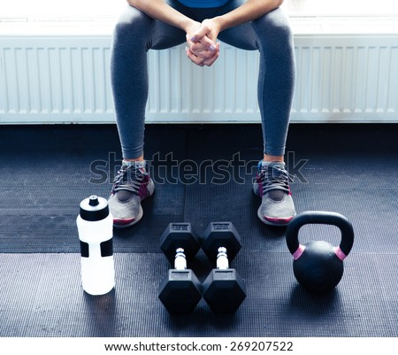 Closeup image of a woman sitting at gym with dumbbells, shaker and weight - stock photo
