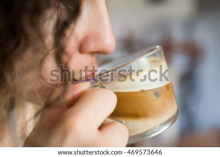 Closeup image of a young woman drinking iced coffee from a glass cup