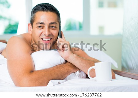 Closeup image of an adult lying in bed while talking by phone with somebody on the foreground  - stock photo