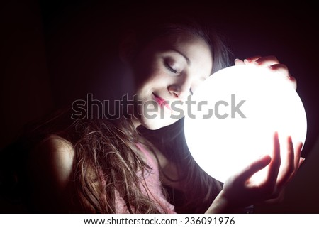 closeup image of beautiful young sleeping woman holding ball of light and happy smiling - stock photo