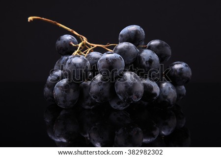 Closeup image of black grapes on black background with reflection - stock photo