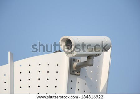 Closeup image of CCTV security camera outdoor with blue sky