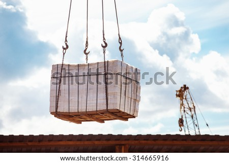 Closeup image of crane lifting heap of bricks at blue sky summer background. - stock photo