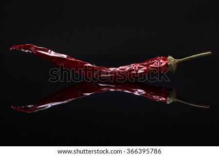 Closeup image of dried red hot pepper on black background with reflection - stock photo
