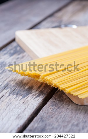 Closeup image of dry pasta on wood table.