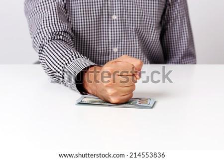 Closeup image of fist on a bills of dollars  - stock photo
