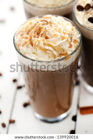 Closeup image of ice coffee with whipped cream and coffee beans - stock photo