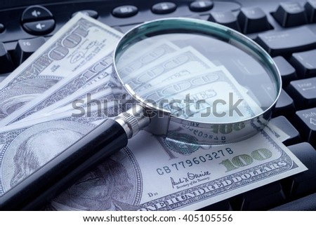 Closeup image of magnifying glass on computer keyboard with hundred dollar bills. Selective focus. - stock photo