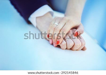 Closeup image of man and woman hands with wedding ring holding tenderly at blue background. - stock photo
