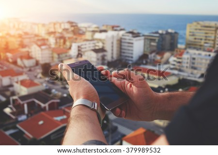 Closeup image of man's hands holding mobile phone with blank copy space screen for your text message or content, young male chatting on cell telephone while looking on city from building's high floor - stock photo