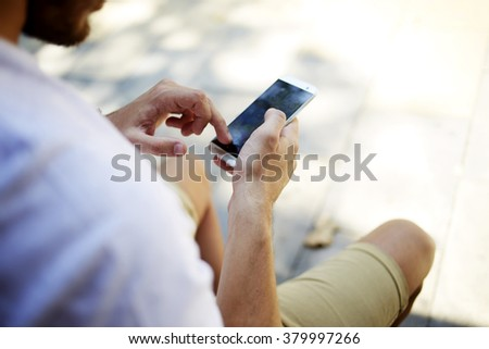 Closeup image of man's hands using mobile phone with blank copy space screen for your advertising text message or content, hipster guy searching information on cell telephone while sitting outdoors - stock photo