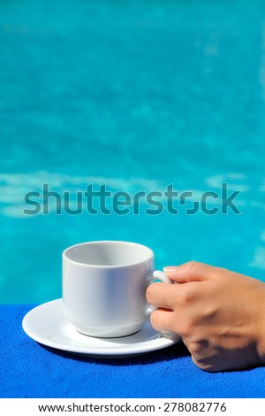 Closeup image of real attractive female beauty holding cup of coffee near swimming pool