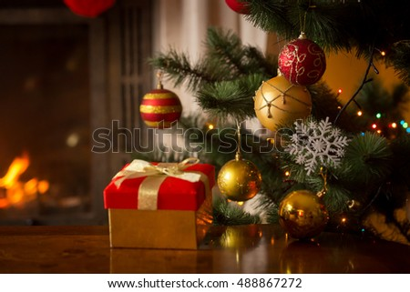 Closeup image of red Christmas gift box with golden ribbon next to decorated Christmas tree and burning fireplace