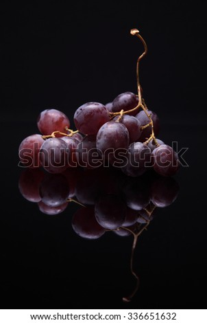 Closeup image of red grapes on black background with reflection - stock photo