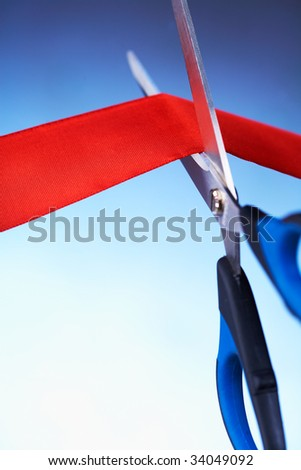 Closeup image of scissors cutting a red ribbon - stock photo