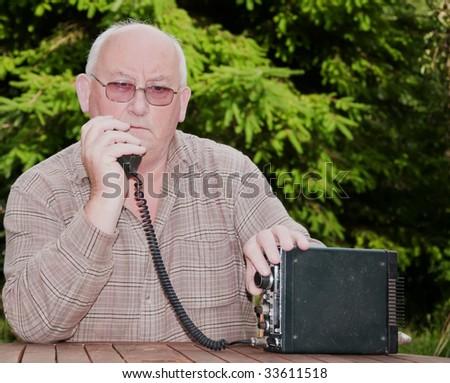 closeup image of senior making amateur radio 2way call - stock photo